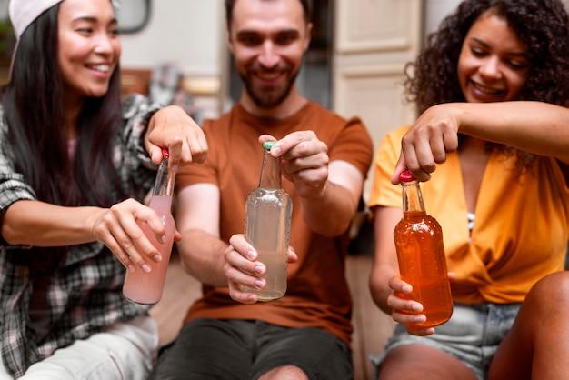 Gelukkig drie vrienden die hun drankjes openen