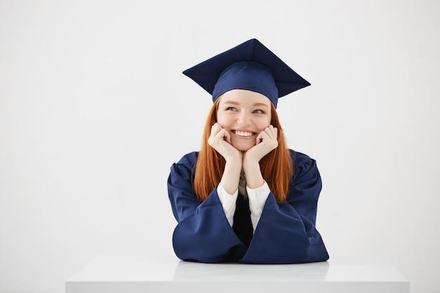 Gelukkig dromerige vrouw afgestudeerd denken dromen dromen zittend.