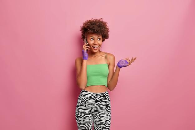 Gelukkig dromerige vrouw met krullend haar geniet van telefoongesprek, steekt hand op en glimlacht positief, gekleed in sportkleding, heeft een slank figuur