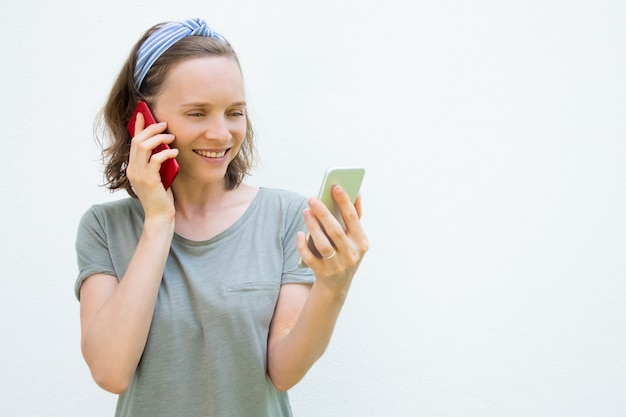 Gelukkig drukke jonge vrouw met behulp van twee mobiele telefoons