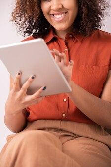 Gelukkig elegante jongedame met krullend haar en brede glimlach scherm van tablet aan te raken tijdens het scrollen door berichten in sociale netwerken