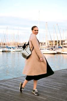 Gelukkig elegante jongedame wandelen in luxe jachtclub van barcelona, vacht sneakers en rugzak dragen, toeristische middenseizoen.