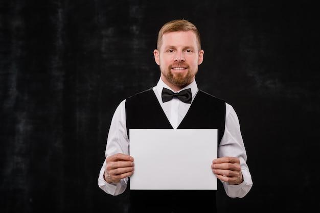 Gelukkig elegante ober van stijlvol restaurant in zwart vest en bowtie met blanco papier terwijl je voor de camera staat