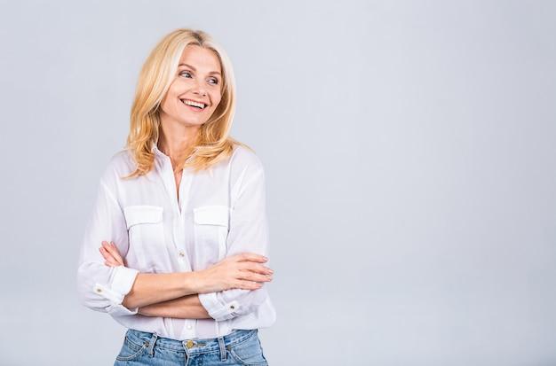 Gelukkig elegante volwassen senior zakenvrouw die lacht staande geïsoleerd op een witte achtergrond. glimlachende zelfverzekerde vrolijke dame van middelbare leeftijd met een witte glimlach die naar de camera kijkt, kopieer ruimte.