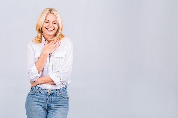 Gelukkig elegante volwassen senior zakenvrouw die lacht staande geïsoleerd op een witte achtergrond. glimlachende zelfverzekerde vrolijke dame van middelbare leeftijd met witte glimlach, kopieer ruimte.