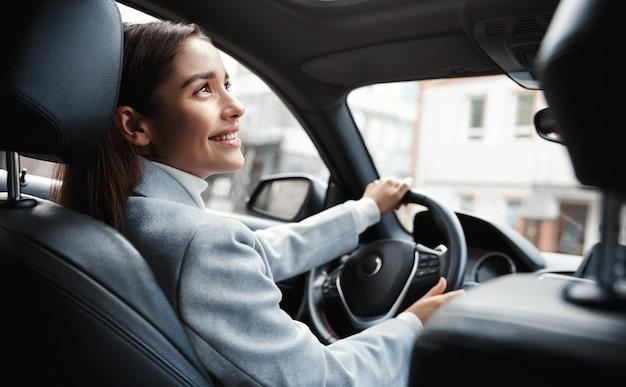 Gelukkig elegante vrouw bestuurder kijken persoon zit in haar auto