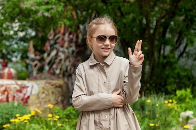 Gelukkig emotie tienermeisje in casual kleding en zonnebril op straat in de stad. zomerse stadswandelingen in de buurt van huis. concept van kindertijd en ouderschap. ruimte kopiëren