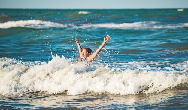 Gelukkig emotioneel meisje baadt in de schuimende stormachtige golven van de zee op een zonnige warme zomerdag. het concept van langverwachte vakantie en reizen met kinderen