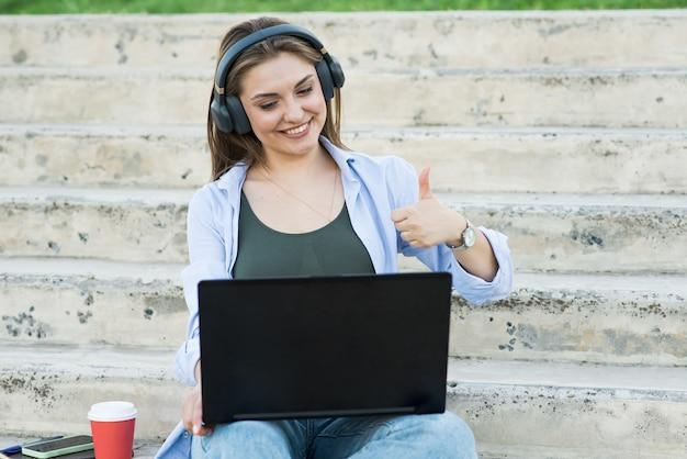 Gelukkig en aantrekkelijk kaukasisch meisje zit met een laptop op de trap en praat. duim omhoog, overeenkomst. werken op afstand. freelance concept