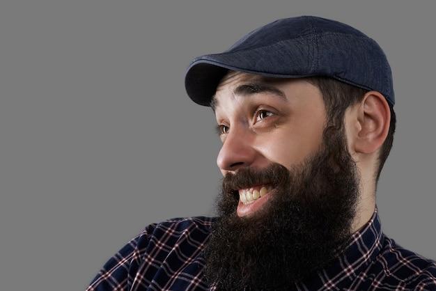 Gelukkig en gek close-up bebaarde mannelijke gezicht. man verrast door kleine prijzen voor goederen. week van verkoop concept. de kerel heeft een grappige glimlach die op grijze achtergrond wordt geïsoleerd. kopieer ruimte voor reclametekst