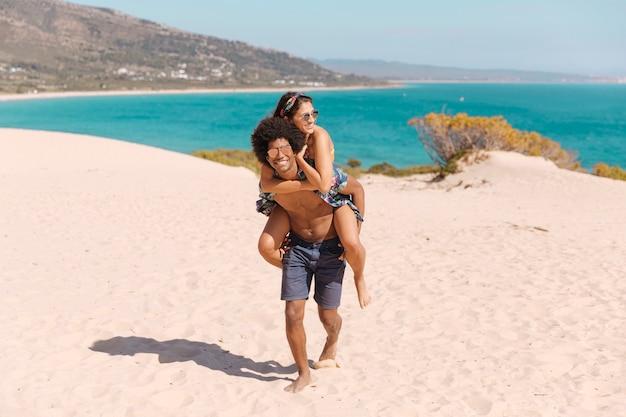 Gelukkig en glimlachend kerel dragend meisje op terug op strand