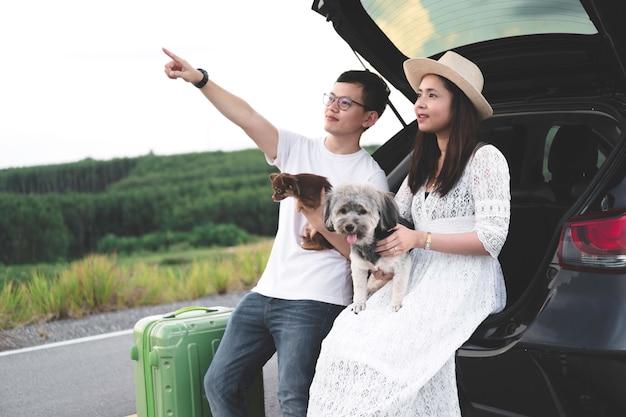 Gelukkig en jong aziatisch paar dat het leven van reis met huisdieren geniet.