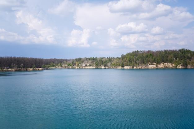 Gelukkig en jong meisje en jongen hand in hand en lachen, op de achtergrond van een meer en een groene weide. een paar staat in een weiland. vrolijke zomerdag