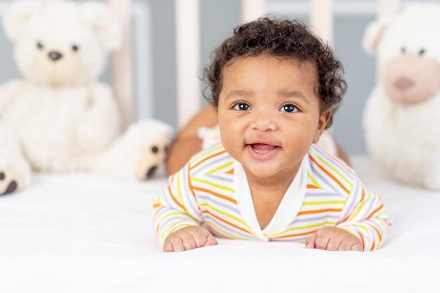 Gelukkig en lachende afro-amerikaanse kleine baby in bed met speelgoed