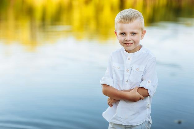 Gelukkig en mooi jongetje in de buurt van het meer