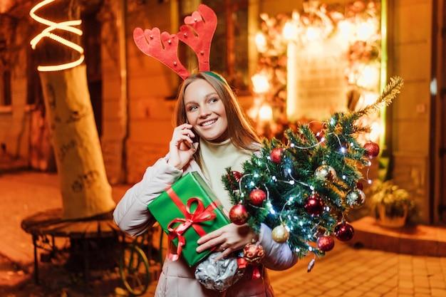 Gelukkig en mooi kaukasisch meisje dat een kerstboom houdt en aan de telefoon spreekt