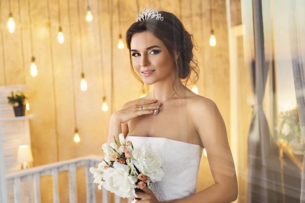 Gelukkig en mooie bruid met boeket bloemen