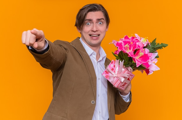 Gelukkig en opgewonden jonge man met boeket bloemen wijzen