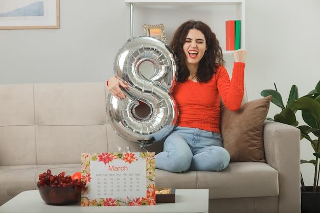 Gelukkig en opgewonden jonge vrouw in casual kleding glimlachend vrolijk zittend op een bank met nummer acht vormige ballon balde vuist in lichte woonkamer vieren internationale vrouwendag 8 maart