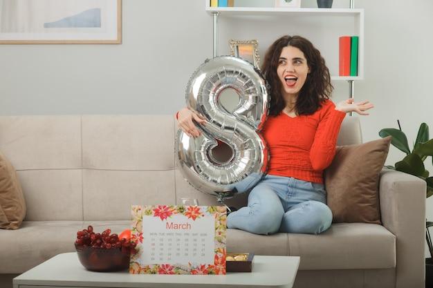 Gelukkig en opgewonden jonge vrouw in casual kleding glimlachend vrolijk zittend op een bank met nummer acht vormige ballon in lichte woonkamer vieren internationale vrouwendag 8 maart