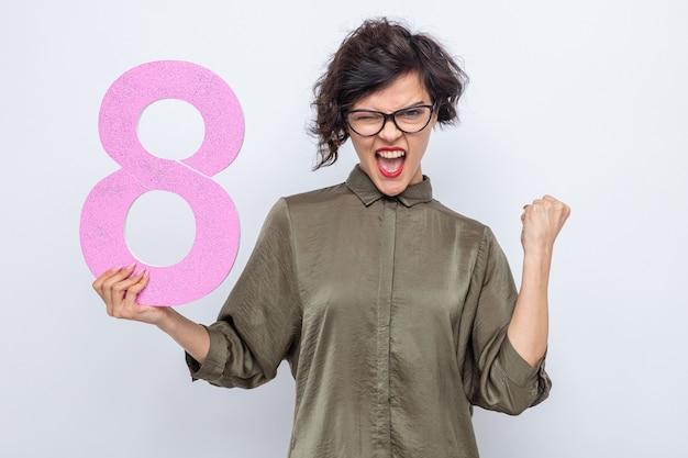 Gelukkig en opgewonden vrouw met kort haar met nummer acht gemaakt van karton kijkend naar camera balde vuist vieren internationale vrouwendag 8 maart staande op witte achtergrond