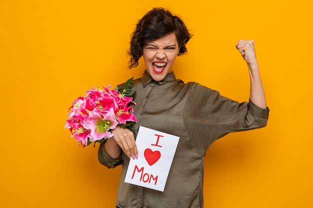 Gelukkig en opgewonden vrouw met kort haar met wenskaart en boeket bloemen kijken camera balde vuist vieren internationale vrouwendag 8 maart permanent over oranje achtergrond