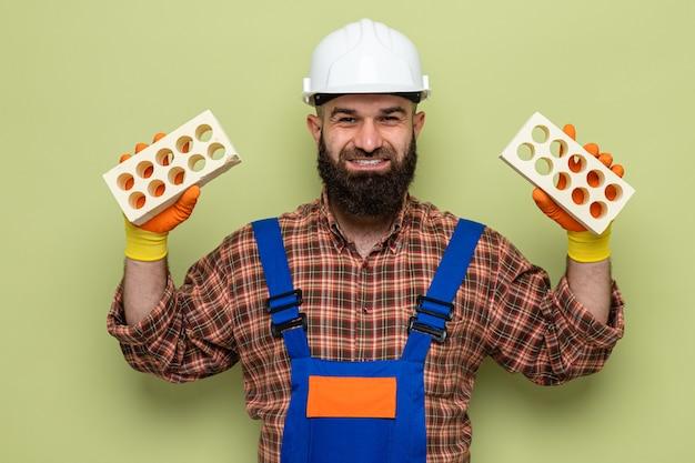 Gelukkig en positieve bebaarde bouwer man in bouw uniform en veiligheidshelm dragen van rubberen handschoenen met bakstenen kijken camera glimlachend vrolijk staande over groene achtergrond