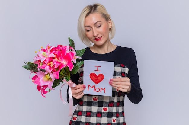 Gelukkig en positieve jonge vrouw in mooie jurk met wenskaart en boeket bloemen glimlachend vrolijk vieren internationale vrouwendag staande over witte muur