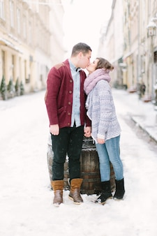 Gelukkig en romantisch kaukasisch paar die in warme sweaters in de winterstad lviv lopen. vakanties, winter, liefde, warme dranken, mensen