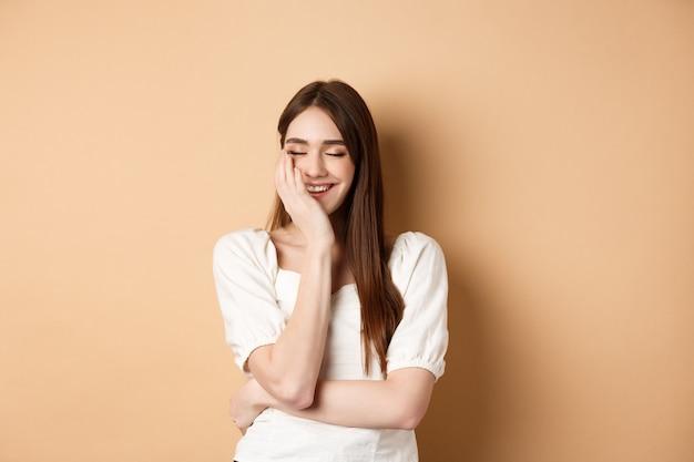 Gelukkig en romantisch meisje dat lacht met gesloten ogen, gezicht aanraakt en vreugde voelt terwijl ze op beige ba...