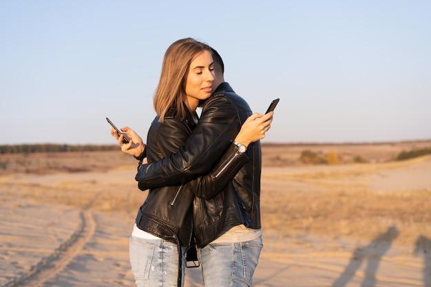Gelukkig en schattig schattig volwassen paar leren jas en jeans man met vrouw vriendin wandelen concept over hoe mobiele telefoons sociale netwerken