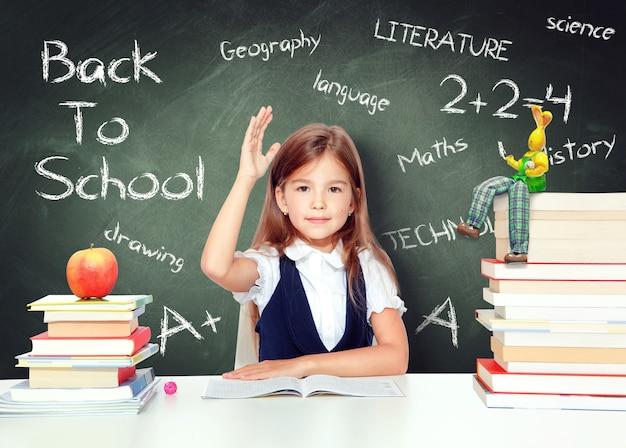 Gelukkig en schattig tienerschoolmeisje dat hand opsteekt in de klas