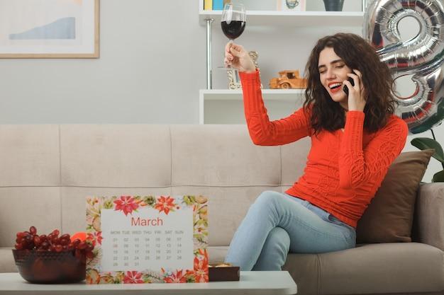 Gelukkig en tevreden jonge vrouw in casual kleding glimlachend vrolijk zittend op een bank met glas wijn praten op mobiele telefoon in lichte woonkamer vieren internationale vrouwendag 8 maart
