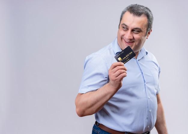 Gelukkig en tevreden man van middelbare leeftijd met een blauw shirt met een creditcard o een witte ruimte