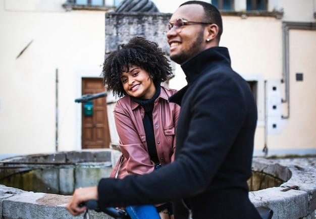 Gelukkig en tevreden zwarte etnische paar zittend op de fiets.