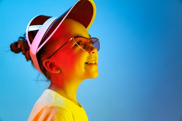 Gelukkig en tienermeisje permanent en glimlachend geïsoleerd op trendy blauwe neon studio