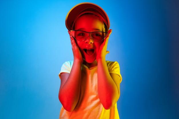 Gelukkig en tienermeisje permanent en glimlachend geïsoleerd op trendy blauwe neonruimte. mooi vrouwelijk portret. jong stel tevreden meisje