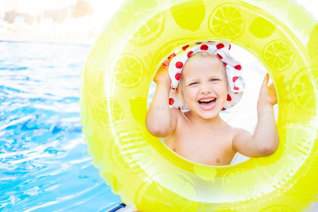 Gelukkig en vrolijk babymeisje kijkt uit de opblaasbare gele cirkel bij het zwembad in de zomer en glimlacht, het concept van reizen en recreatie