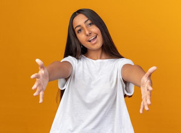Gelukkig en vrolijk jong meisje in een wit t-shirt dat naar de camera kijkt en een verwelkomend gebaar maakt met handen die over een oranje achtergrond staan