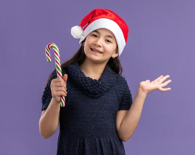 Gelukkig en vrolijk meisje in een gebreide jurk met een kerstmuts die een snoepriet vasthoudt met een glimlach op het gezicht dat over een paarse muur staat