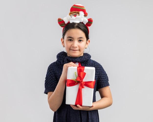 Gelukkig en vrolijk meisje in gebreide jurk, gekleed in rode stropdas met grappige kerst rand op hoofd met kerstcadeau op zoek met een glimlach op het gezicht