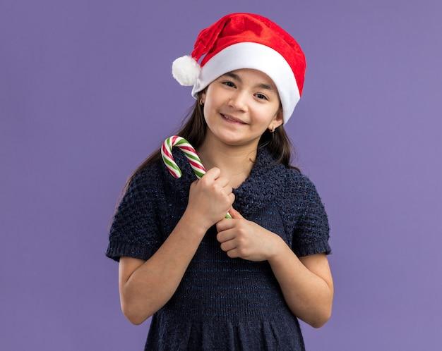 Gelukkig en vrolijk meisje in gebreide jurk met kerstmuts bedrijf candy cane camera kijken met glimlach op gezicht staande over paarse achtergrond