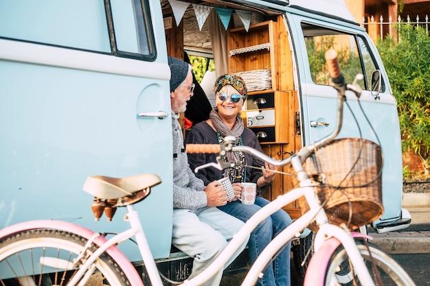 Gelukkig en vrolijk seniorenpaar geniet van het reizen en de gepensioneerde levensstijl die samen een kopje koffie drinkt in een oud busje met een fiets buiten