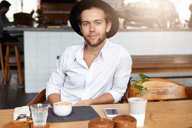 Gelukkig en vrolijke jonge bebaarde man in stijlvolle hoofddeksels met koffie, zittend aan een houten tafel in het moderne café-interieur, wachtend op zijn vriendin, van plan om haar deze zonnige dag voor te stellen