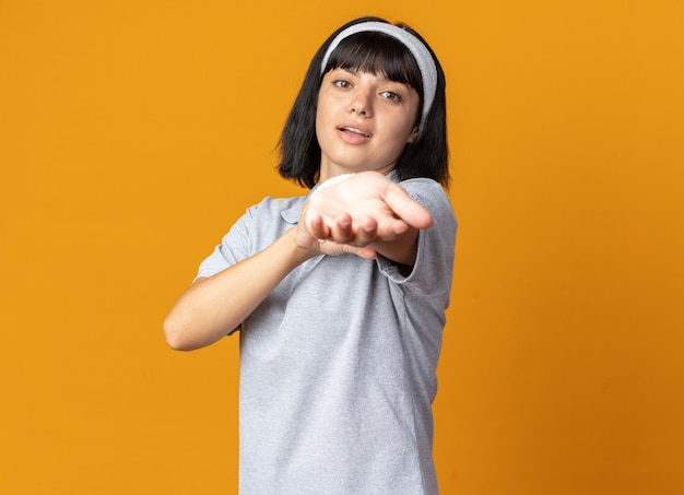 Gelukkig en zelfverzekerd jong fitnessmeisje met een hoofdband die haar handen uitrekt, klaar om te trainen en over oranje te staan