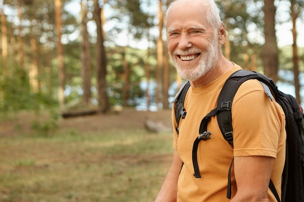 Gelukkig energieke gepensioneerde man met zwarte rugzak achter zijn rug glimlachend breed, genieten van wandelen in het bos op zonnige herfstdag. buiten schot van oudere man met baard wandelen in het bos