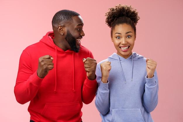 Gelukkig enthousiast enthousiast jong afro-amerikaans koppel balde vuisten vreugdevol verrast winnende geweldige huwelijksreis reiskaartjes permanent roze achtergrond triomfantelijk glimlachend in grote lijnen vieren