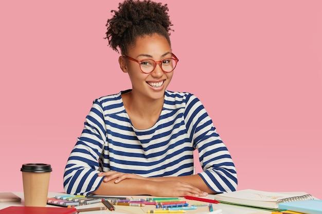 Gelukkig etnische student ontwerper tekent schets voor universitair examen, draagt een gestreepte jas en bril