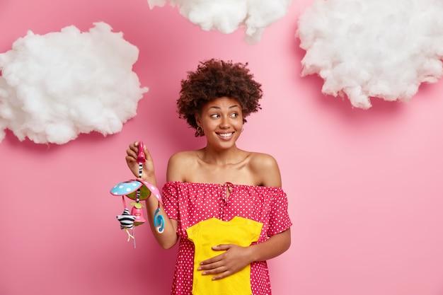 Gelukkig etnische zwangere vrouw houdt gele romper en mobiel voor toekomstige baby, geniet van kinder anticipatie, kijkt opzij met glimlach, draagt polka dot jurk, heeft grote buik, wordt op het derde trimester
