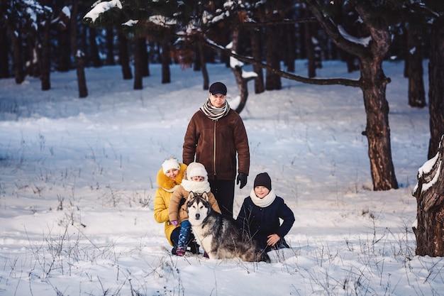 Gelukkig europees jong gezin met grote hond poseren tegen winter dennenbos